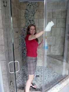 Woman cleaning glass shower